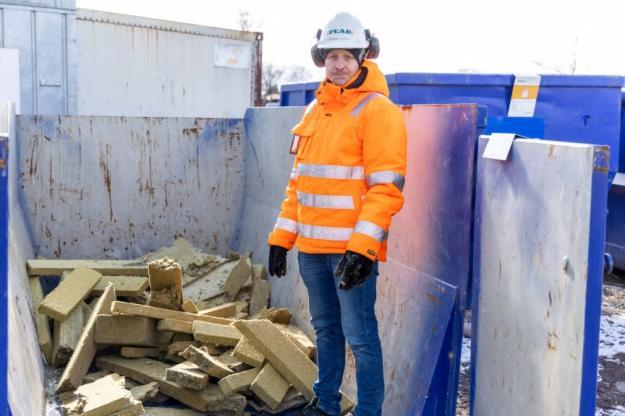 Johannes Larsson granskar containern med stenull som ska återvinnas.